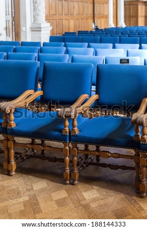 Old style hall wih rows of blue seats - stock photo