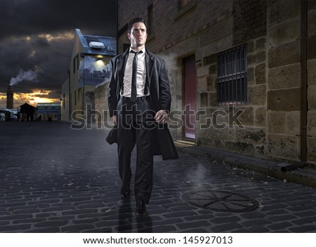 Old style man in factory area wearing a black suit and coat - stock photo