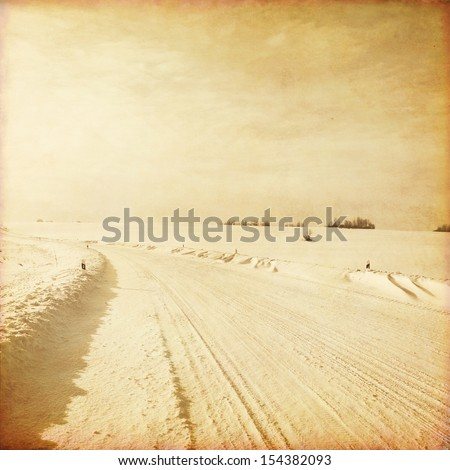 Old style photo of empty winter road. - stock photo