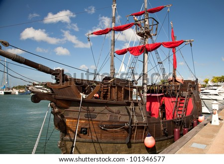 Old Style ship with red sail - stock photo