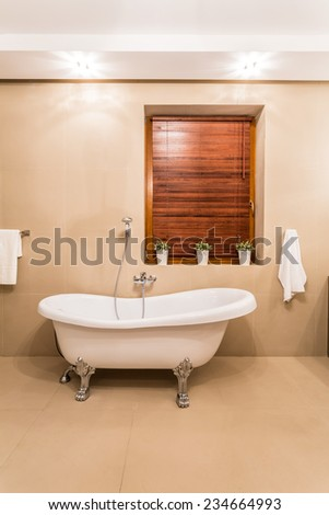 Old style white bathtub in modern bathroom - stock photo