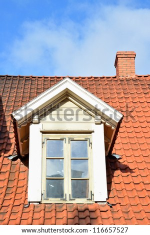 Old style window on the red tile roof - stock photo
