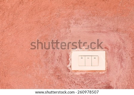 Old Switch on orange cement wall - stock photo