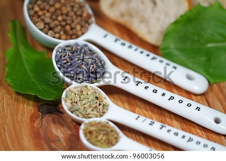 Old table-top selection of herbs and grains in measuring spoons - stock photo