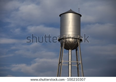 Old tall silver water tower with cloudy blue sky background - stock photo