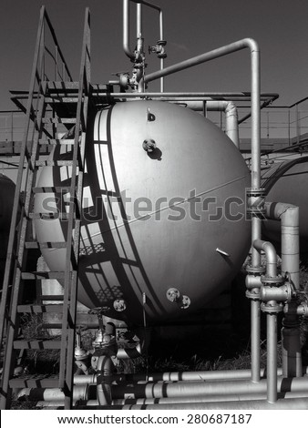 old tank and rusty ladder on the gas-filling stations. Black and white photo - stock photo