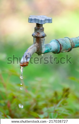 Old tap with leaking water. Closeup with shallow DOF. - stock photo