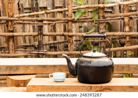 Old tea kettle with glass outdoor - stock photo