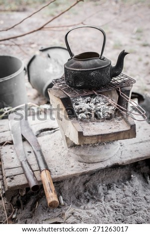 Old teapot boils on campfires,knife. - stock photo