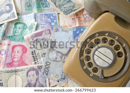Old Telephone on money of various country, Business concept - stock photo