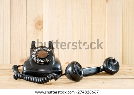 Old telephone on wood background. - stock photo