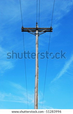 old telephone pole against blue sky - stock photo
