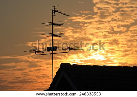 Old television antenna (Fishbone) on the roof against sunrise - stock photo