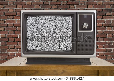 Old television with static screen and brick wall. - stock photo