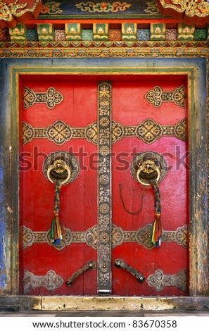 Old temple door decorated with tassels at Buddhist monastery, Tibet - stock photo
