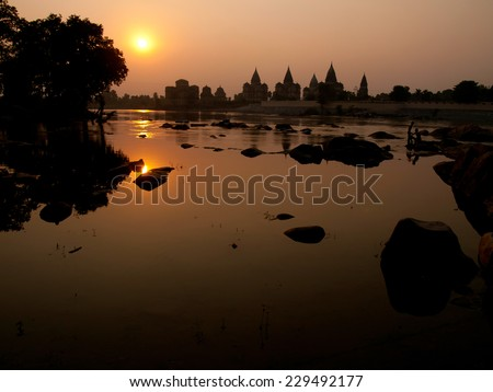old temples during sunset at the river in Orchha, India - stock photo