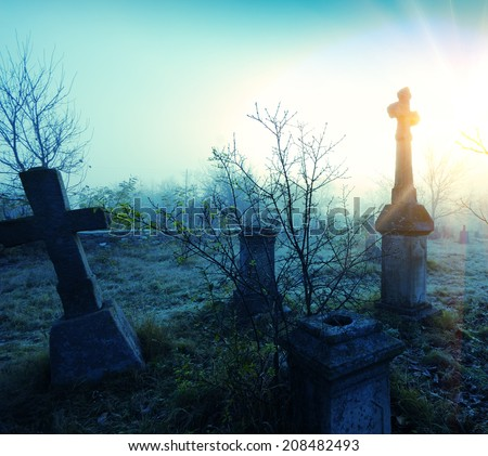 Old terrible stone cross on cemetery on background of sky and sunlight - stock photo