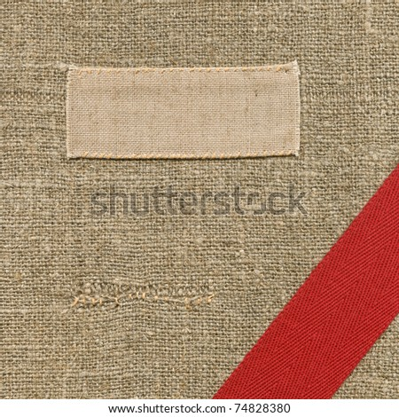 Old textile tag with a ribbon in the corner - stock photo