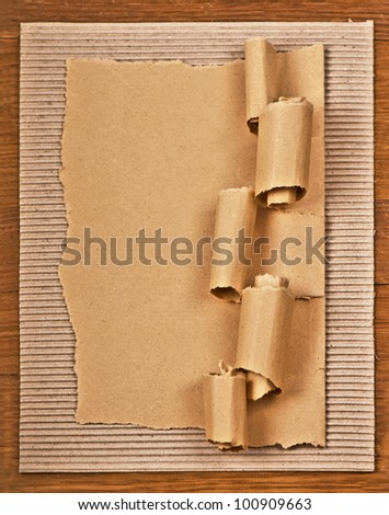 old textured cardboard sheet with torn edges wooden background (with space for text) - stock photo