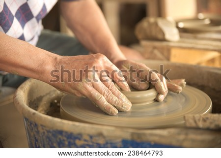 Old Thai male hand shaping a dish from gray color clay. - stock photo