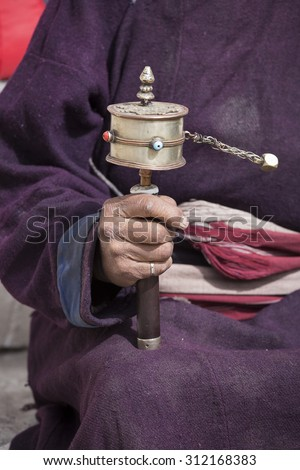Old Tibetan man holding buddhist prayer wheel in Lamayuru Gompa, , Ladakh, India. Hand and prayer wheel, close up - stock photo