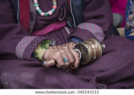 Old Tibetan woman holding buddhist prayer wheel in Lamayuru Gompa, , Ladakh, India. Hand and prayer wheel, close up - stock photo