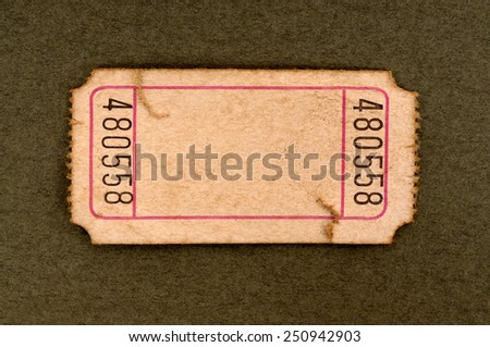 Old ticket : torn blank movie or raffle ticket isolated on a brown background.  Space for copy.  - stock photo