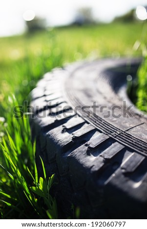 Old tire in grass - stock photo