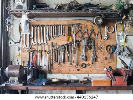 Old tools hanging on wall in workshop , Tool shelf against a wall - stock photo