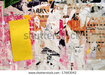 Old torn advertisements on a wall with yellow copy space - stock photo