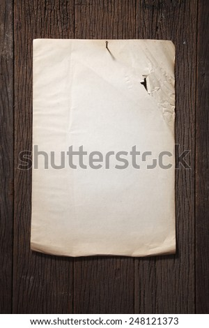 old torn paper on the wooden wall - stock photo