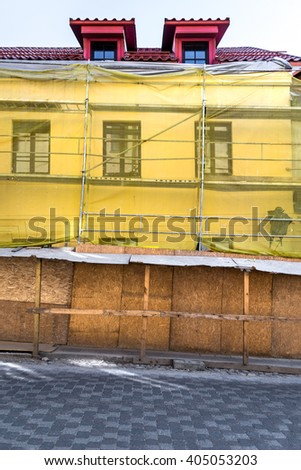 Old town european building reconstruction site with scaffolding in an empty tiled street - stock photo