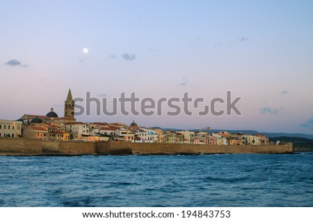 Old Town of Alghero (Sardinia Island, Italy) in the moonlight of sunset. Defensive wall of the city. The view from Mediterranean sea.  - stock photo