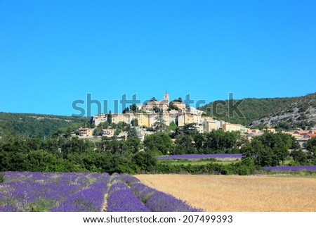 old town on the hill with lavender and wheat farms at Banon, France. - stock photo