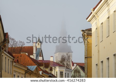 Old Town roofs and St. Nicholas Church or Niguliste folded in morning mist, Tallinn, Estonia - stock photo