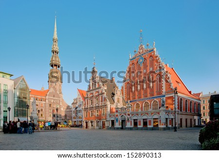 Old town square in the center of Riga, Latvia. Tourist attractions House of Blackheads and St Peters church. - stock photo