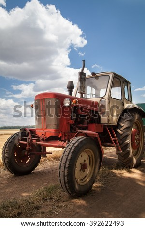 old tractor on the field, against a cloudy sky - stock photo