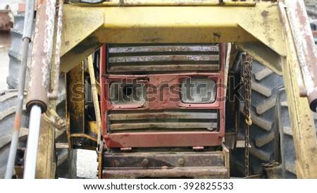 Old tractor with headlight broken - stock photo