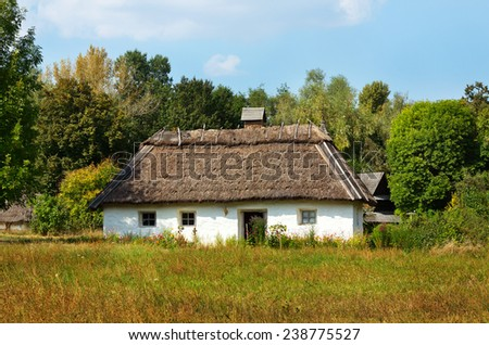 Old traditional ukrainian rural cottage with a straw roof - stock photo