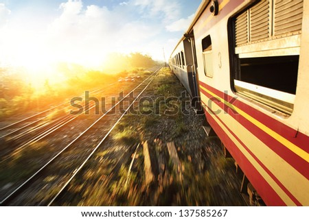 Old train with motion blurred ground and blue cloudy sky at sunrise - stock photo