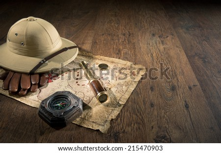 Old treasure map with colonial style pith hat, bras telescope and compass. - stock photo