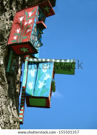 Old tree with many colored bird houses - stock photo