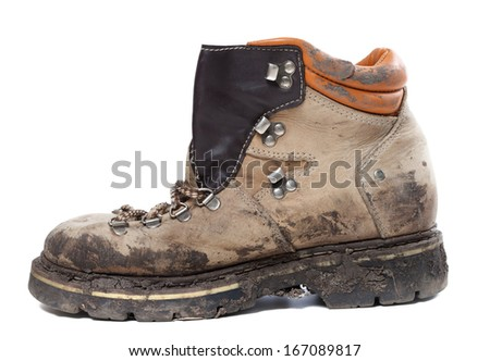 Old trekking boot in mud. Isolated on white background. Side view. - stock photo