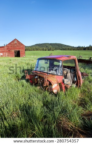 Old truck in grass near a red barn south of Tensed, Idaho. - stock photo