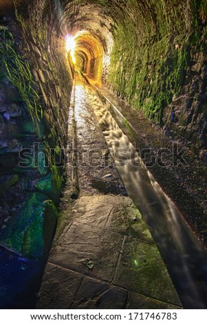 old tunnel moistened with water channel carved in the rock - stock photo