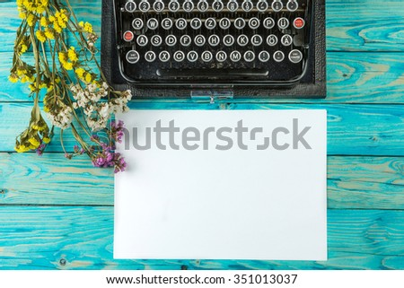 Old typewriter and a blank sheet of paper, retouching author writer. Blue wooden table dry flowers. Top view. The creative process of writing a new novel - stock photo