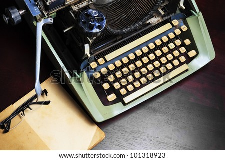 Old typewriter and old book on the table. - stock photo