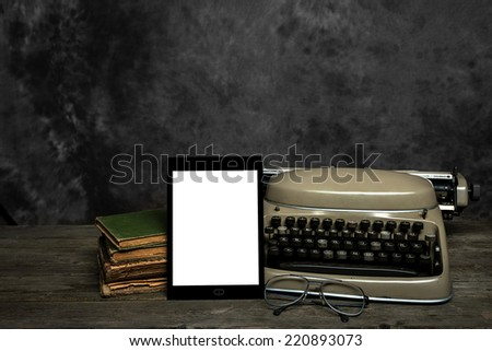 Old typewriter, old books, reading glasses and an self-designed E-Reader with blank display - stock photo