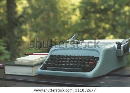 old typewriter on a wooden garden table with books  - stock photo