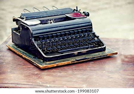 Old typewriter on the table, vintage style  - stock photo